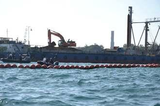 台船に積まれた大量の土砂をショベルカーがトラックに積み替えた=27日午前10時ごろ、名護市辺野古沖