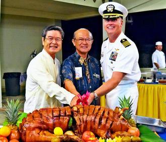 豚が550頭届けられたことにちなみ、豚の丸焼きに入刀するロバート・マシューソン司令官(右)、島袋俊夫うるま市長(中央)、沖縄ハワイ協会の山内彰会長=17日、うるま市勝連の米軍ホワイトビーチ