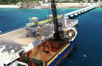 民間桟橋で、辺野古沿岸部を埋め立てる土砂を運搬用船に積み込む作業が始まった=3日午前11時35分(小型無人機で撮影)