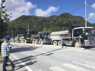 土砂を搬入するため、琉球セメント桟橋に向かうダンプトラックが列をなした=22日午前、名護市安和