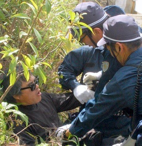 目取真俊さん(左端)を4人がかりで押さえ込む警察官=18日、東村高江・米軍北部訓練場N1地区表側出入り口