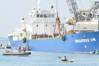 土砂を辺野古に運ぶ運搬船(奥)を阻止しようと近づく市民のカヌー(手前右)=27日、名護市安和