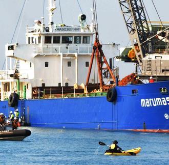 土砂を辺野古に運ぶ運搬船(奥)を阻止しようと近づく市民のカヌー(手前右)=2月27日、名護市安和
