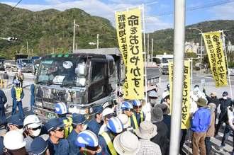 抗議の中、辺野古新基地埋め立て用土砂を琉球セメントの桟橋に運び込むダンプ=20日、名護市安和