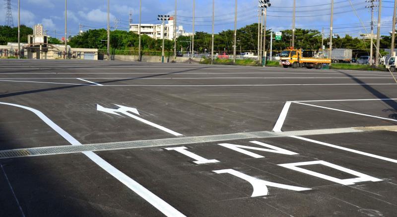 アスファルトが敷かれ、仮駐車場になった沖縄市サッカー場跡地=23日、沖縄市諸見里