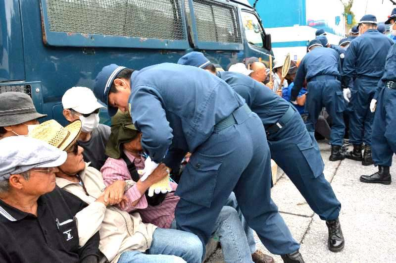 座り込み抗議する市民を強制排除する機動隊員ら=4月27日、名護市辺野古キャンプ・シュワブゲート前