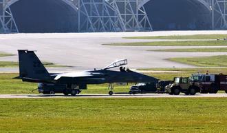最初に着陸したF15戦闘機。消防車両などが待機する中、緊急点検を受ける=15日午前10時43分、嘉手納基地(読者提供)