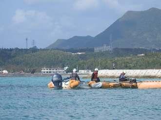 オイルフェンスを設置する作業員=14日午前10時、名護市辺野古米軍キャンプ・シュワブ沖