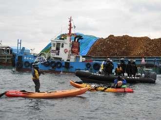 埋め立て用の土砂を積んだ台船の接岸に抗議するカヌーチーム=22日午前、名護市辺野古の米軍キャンプシュワブ沿岸