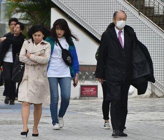 時折吹く強い風に背中を丸めながら歩く人たち=9日午後、那覇市久茂地