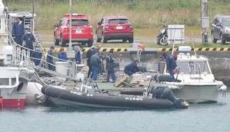 係留中のゴムボートなどを調べる海保職員や捜査員ら=16日午前10時53分、名護市城・名護漁港