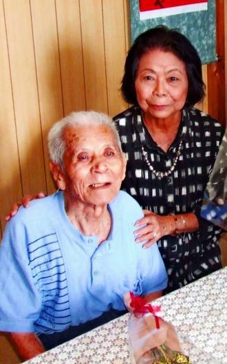 再会を果たした金城盛徳さん(左)の肩に手を置く長峯文子さん=18日、うるま市昆布の金城さんの自宅