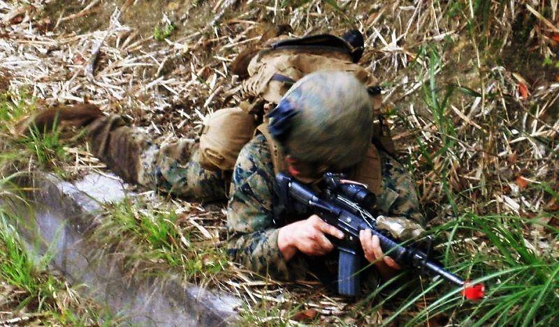 車道の脇にうつぶせになり、銃を構える米兵=20日、国頭村安波(高江現地行動連絡会提供)