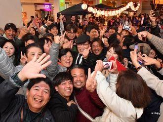 親指を立て上機嫌の吉田類さん(中央)を囲む、ほろ酔いの人たち=1日午後9時8分、沖縄市(落合綾子撮影)