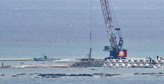工事が始まった「K8」護岸。クレーンが汚濁防止膜をつり下げ、海面に下ろす=4日午後2時10分、名護市辺野古の沖合(田嶋正雄撮影)